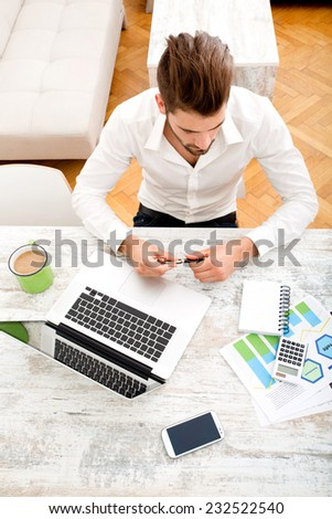 A young man sitting at the table with a laptop computer.  - stock photo