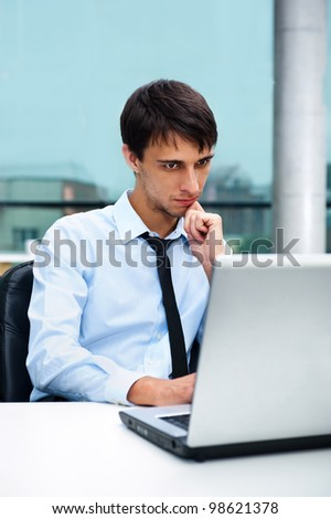 A young man sitting in front of a laptop at office - stock photo