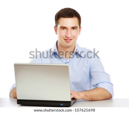 A young man sitting in front of a laptop, isolated on white background