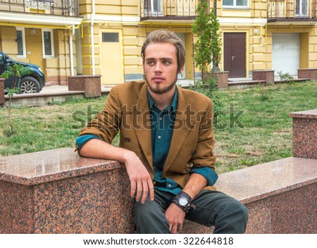 A young man sitting on a bench in the city - stock photo