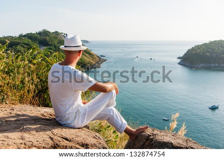 a young man sitting on a rock and looking at the sunset of Phuket - stock photo