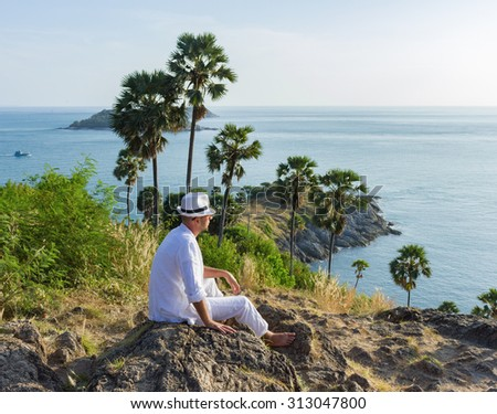 a young man sitting on a rock and looking at the sunset of Phuket