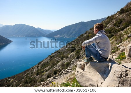 A young man sitting over the sea at the rock and contemplating beautiful Kotor bay in Montenegro - stock photo