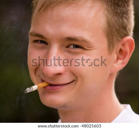 A young man smoking cigarette, focus is set at his face