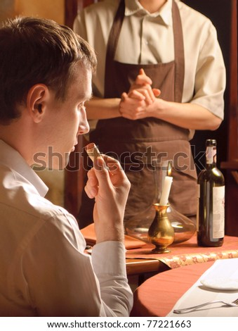 A young man sniffing the cork of a wine bottle - stock photo