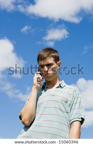 A young man speaks by phone on a background sky.