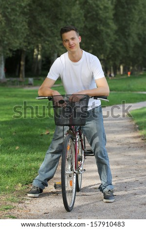 A young man standing at a bike in a park
