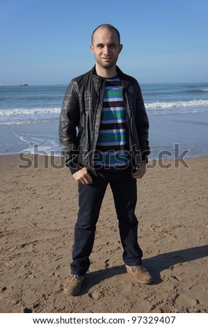 A young man standing by a beach