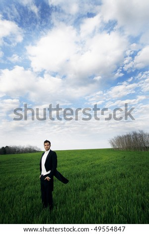 A young man standing in a field wearing a tuxedo.