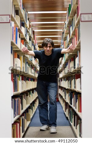 A young man standing in the aisles of the library book shelves.