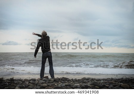 A young man standing on the sea shore