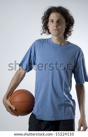 A young man, stands holding a basketball, staring at the camera. Vertically framed shot. - stock photo