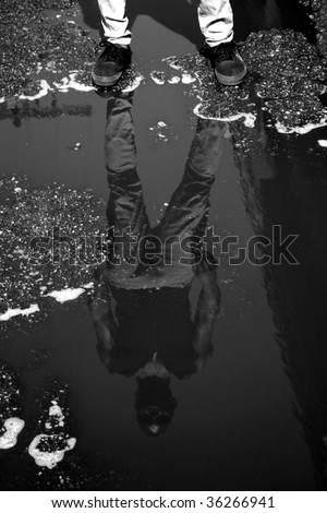 a young man stands in an alley with his reflection in a puddle - stock photo
