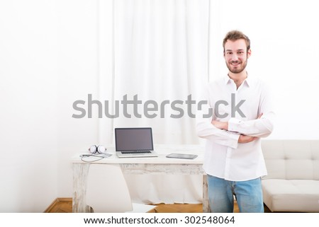 A young man starting his business from home. - stock photo