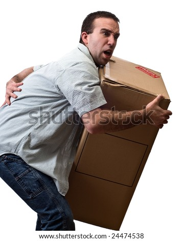A young man suffering from back pain while lifting a large box, isolated against a white background - stock photo