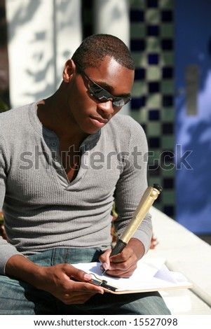 a young man takes notes on a sheet of paper with a giant pen
