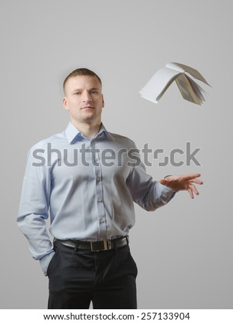 A young man throws the book over his head. On a white background - stock photo