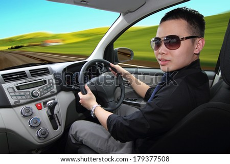 A young man turning to look back at passenger while driving - stock photo