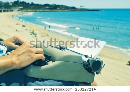 a young man typing in an old typewriter on the beach - stock photo