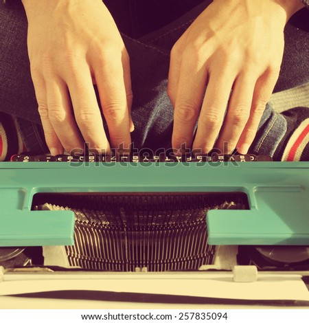 a young man typing in an old typewriter on the bed, with a retro effect - stock photo