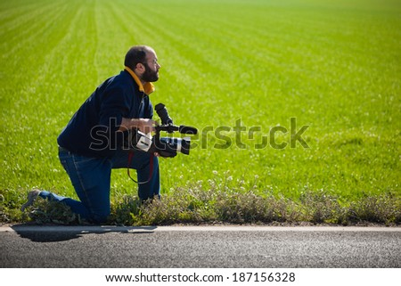 a young man using a professional camcorder outdoor - stock photo