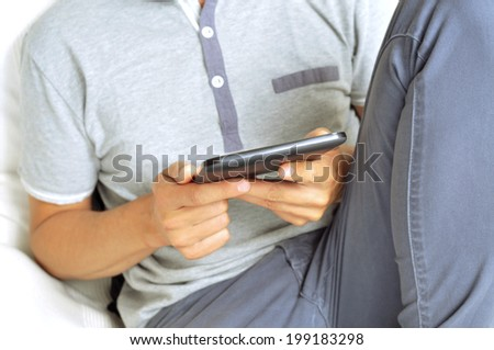 a young man using a tablet computer - stock photo