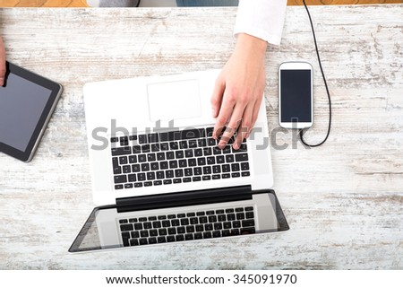 A young man using his laptop computer and various other devices on a desktop.	