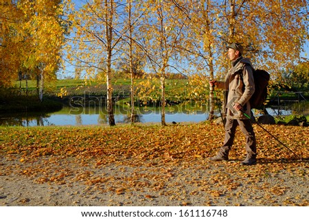 A young man walking along the lake. Golden autumn.