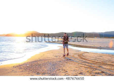 A young man walking on the beach at sunset.