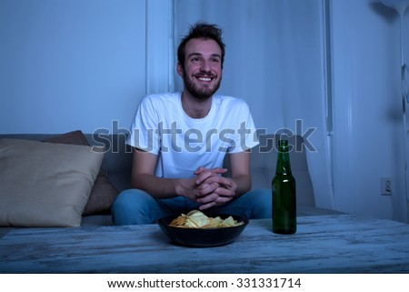 A young man watching TV at nighttime at home in the living room.