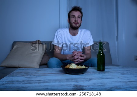 A young man watching TV at nighttime with potato chips and beer at home in the living room.