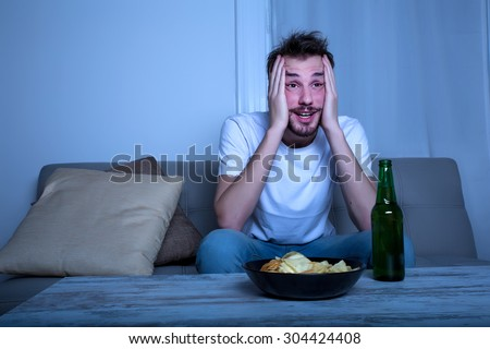 A young man watching with passion TV at nighttime with potato chips and beer at home in the living room.