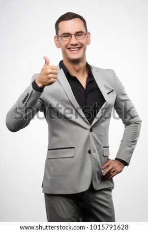 A young man wearing a gray suit and glasses shows a sign thumb up. Copy space. Isolated on white. Advertising, fashion and commercial Design,