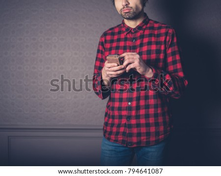 A young man wearing a red flannel shirt is at home in a luxury living room using his smart phone