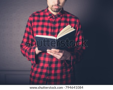 A young man wearing a red flannel shirt is reading a book in a luxury living room