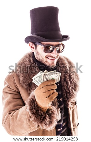 a young man wearing a sheepskin coat and a top hat isolated over a white background holding banknotes - stock photo