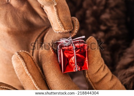 a young man wearing a sheepskin coat and holding a very small christmas gift - stock photo