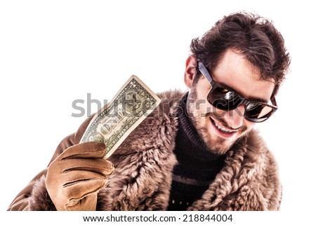 a young man wearing a sheepskin coat isolated over a white background holding banknotes - stock photo