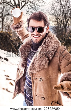 a young man wearing a sheepskin coat  playing with a snowball - stock photo