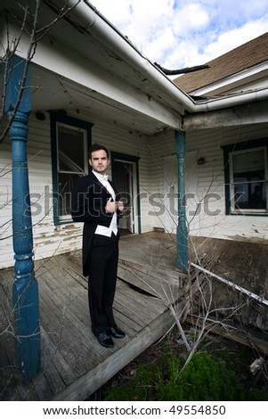A young man wearing a tuxedo standing in front of an abandoned house.
