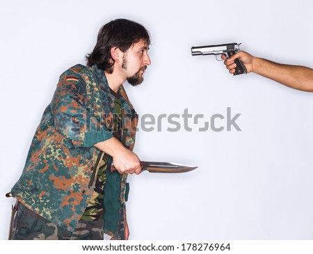 A young man wearing camouflage clothes and holding a dagger in his hand is threatened with a gun pointed to his head by another unknown man - isolated on white - stock photo