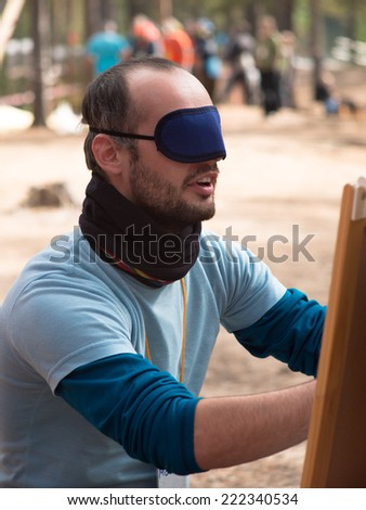 A young man with a bandage over his eyes and mouth open doing something hands - stock photo