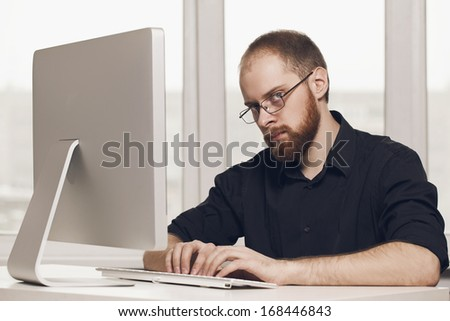 a young man with a beard on the computer