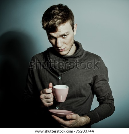 A young man with a cup of coffee - stock photo