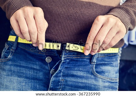 a young man with a measuring tape as a belt tries to fasten his trousers, because of the weight gain - stock photo