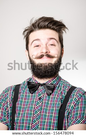 A young man with a nerdy look smiling at the camera - stock photo