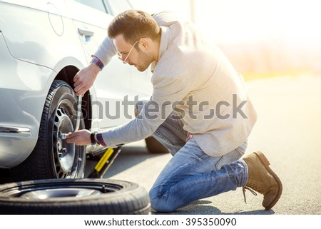 A young man with a silver car that broke down on the road.Changing tire on broken car on road. - stock photo