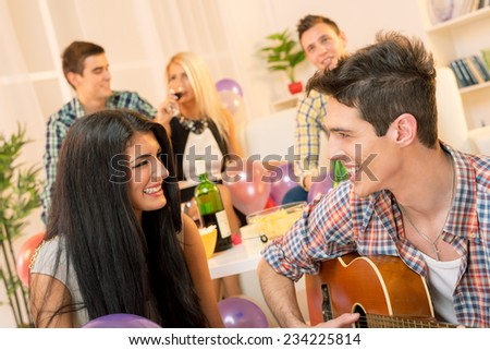 A young man with an acoustic guitar, at home party, courting a pretty girl playing to her. In the background you can see young people sitting on the couch and enjoy the atmosphere of home party. - stock photo