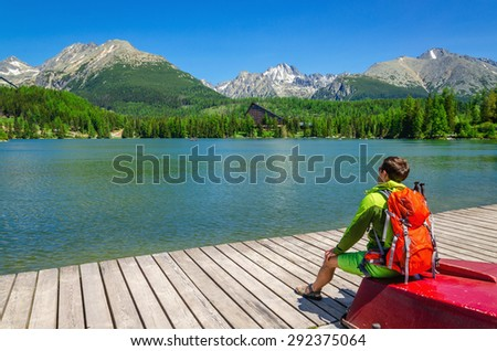 A young man with an orange backpack sitting on a red boat at the pier of mountain lake Strbske Pleso, Slovakia