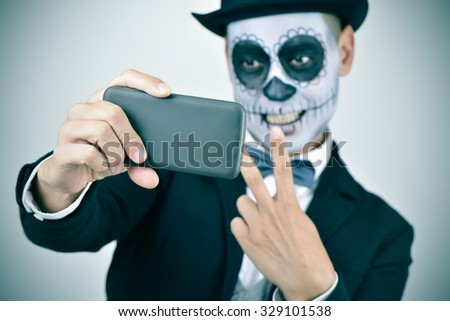 a young man with calaveras makeup, wearing bow tie and top hat, takes a selfie of himself with a smartphone - stock photo